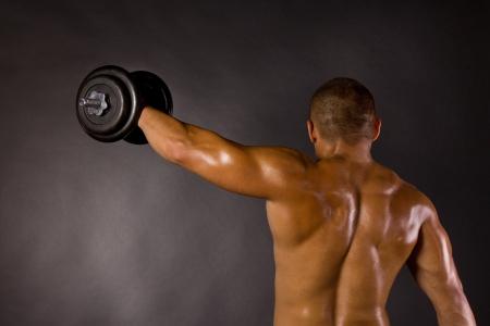 Muscled male bodybuilderweight, dumbbell, raise, swing Stock Photo - 13801883