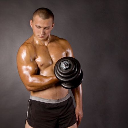 Muscled male bodybuilderweight, dumbbell, raise, swing Stock Photo - 15370166