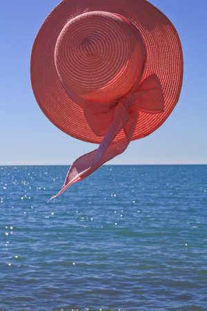 roze hoed tegen de zee