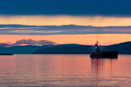Boat  bulk carrier  on the fjords of Norway, mountain in the background with sunset light  photo