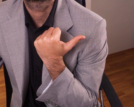 gesticulation: young man in office showing  body language pointing closeup Stock Photo