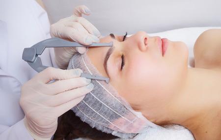 makeup applying: tattooist is using tool to measure eyebrows Stock Photo