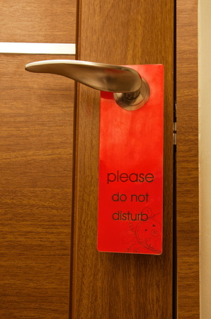 hotel room door: Do not disturb sign on a hotel room door closeup Stock Photo