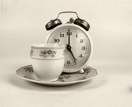 age 5: Tea cup with vintage alarm clock shows 5 oclock tea time
