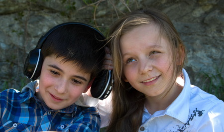 litle: Little boy listens music with earphones and litle girl tryes to hear what does he leaten to