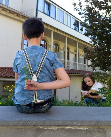 gir: Teenage boy hidesa flower behind his back for teenage gir Stock Photo