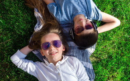 chillout: Little teenage boy and girl are lying on grass and boy wears earphones chillout top view