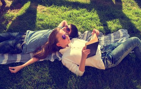 chillout: Little teenage boy and girl are lying on grass, girl reads book and boy wears earphones chillout Stock Photo