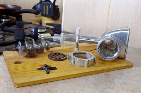 disassembled: disassembled meat grinder on a chopping board