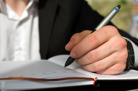 left handed: Left handed businessman is writing something in a notebook
