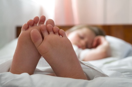 little girls feet who sleeps inher bed closeup