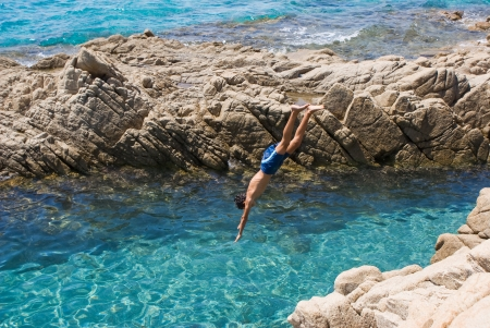 cliff jumping: Plunge of a young boy from a cliff in a beautiful blue sea