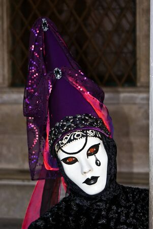 Carnival mask in a black and purple costume, Venice in Italy