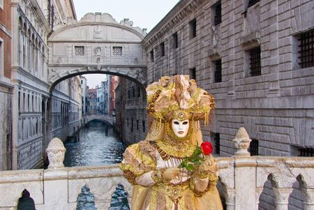 Carnival mask in a yellow costume in front of the  Ponte dei Sospiri , Venice in Italy