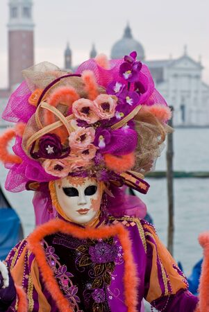 Carnival mask in a colorful costume in front of the Venice lagoon, Italy Stock Photo - 13512726