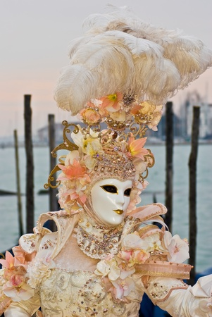 Carnival mask in a colorful costume in front of the Venice lagoon, Italy Stock Photo - 13512730