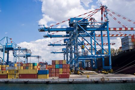 Cranes load a merchant ship in a commercial port terminal, Naples in Italy