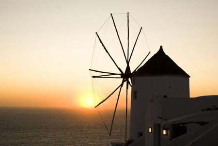 Sunset behind a windmill in Santorini, Greece