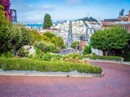 Lombard Street, east west street in San Francisco, California famous for a steep, one block section with eight hairpin turns. Victorian houses and bay in the background. Archivio Fotografico