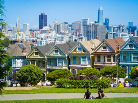 San Francisco, US, Aug 2019: Victorian houses Painted Ladies with downtown and skyscrapers in the background. Also called Seven Sisters Houses, are Victorian and Edwardian houses repainted