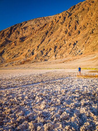 Sexy curvy woman admires the barren salt landscape of Badwater Basin in Death Valley National Park in California, USA. It is one of the hottest places in the world. Banque d'images