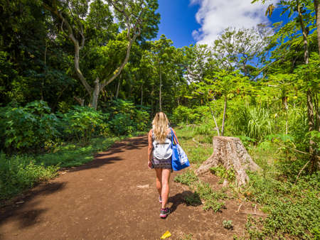 Sexy girl walks into the tropical forest of Honolua Bay in Maui Hawaii. Honolua Bay located north of Kapalua, West Maui Hawaii, United States. Snorkeling paradise in marine and ecosystem preserve.
