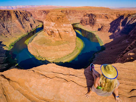 Sexy girl admires panorama of Horseshoe Bend, Page Arizona, the Colorado River and mass made of sandstone