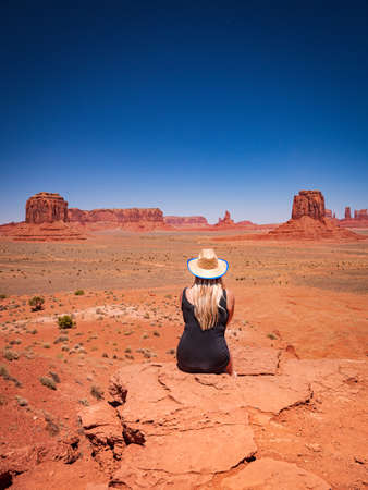 Young blonde girl admires the Monument Valley from Artist's Point, region of Colorado Plateau characterized by cluster of vast sandstone buttes, Arizona Utah border