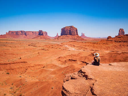 Young blonde girl admires panorama from John Ford Point in Oljato Monument Valley, region of Colorado Plateau characterized by cluster of vast sandstone buttes, Arizona Utah border. 免版税图像