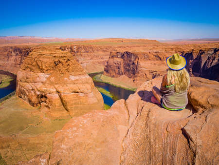 Sexy girl admires panorama of Horseshoe Bend, Page Arizona, the Colorado River and mass made of sandstone, has become major tourist destination. Banque d'images