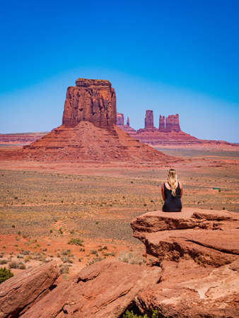 Young blonde girl admires panorama from Artist's Point in Oljato Monument Valley, region of Colorado Plateau characterized by cluster of vast sandstone buttes, Arizona Utah border. Banque d'images