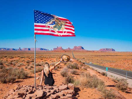 Young blonde girl sits near USA waving flag in Forrest Gump Point Road to Monument Valley, region of Colorado Plateau buttes Arizona Utah border 免版税图像