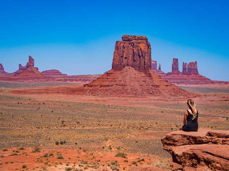 Young blonde girl admires panorama from Artist's Point in Oljato Monument Valley, region of Colorado Plateau characterized by cluster of vast sandstone buttes, Arizona Utah border.