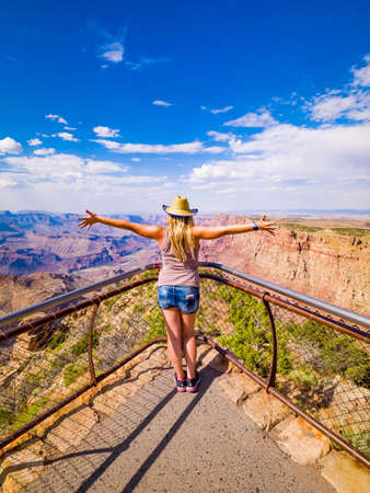 Sexy girl admires panorama of Grand Canyon National Park Desert View Point, northwestern Arizona: View of Steep-sided canyon carved by Colorado River