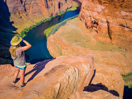 Sexy girl admires panorama of Horseshoe Bend, Page Arizona, the Colorado River and mass made of sandstone, has become major tourist destination.