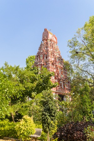 Colorful Hindu Temple through the green trees in city park of Bangalore in bright sunny day, India