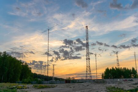 Many huge different antennas under yellow sunset sky at the border of a wood, Moscow District, Russia Stock Photo