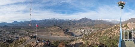 Birds eye view of panoramic mountain valley with small towns under blue cloudy sky, the Andes, Chile