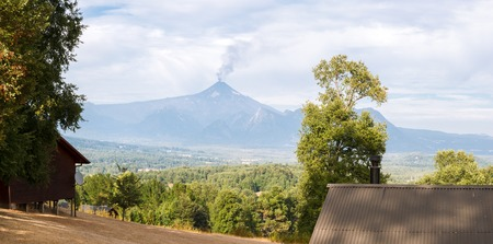 View of the volcano eruption from tourist base on the opposite mountain at noon of summer day in cloudy weather