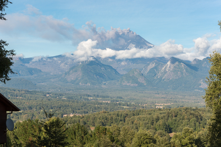 Wide view of volcano eruption from tourist base on the opposite mountain at noon of sunny summer day