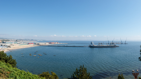 Cargo ships under loading in the port in bright sunny day