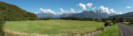 Large green meadow between the mountains Stock Photo