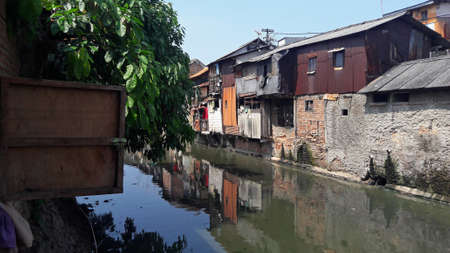 West Jakarta, Indonesia - October 28, 2018 : Slum area located on the banks of a dirty river Éditoriale
