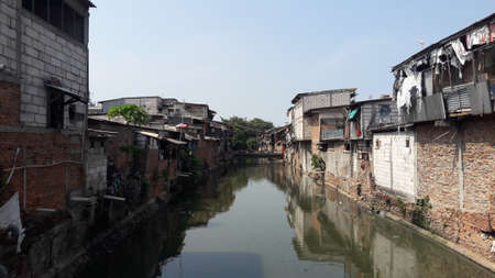 West Jakarta, Indonesia - October 28, 2018 : Slum area located on the banks of a dirty river