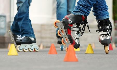 Pattinaggio freestyle slalom è un campo molto tecnico del pattinaggio che prevede l'esecuzione di trucchi attorno ad una linea retta di coni equidistanti Archivio Fotografico - 10810551
