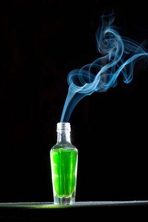 Fumo intrecciato dalla bottiglia. Isolato su nero.