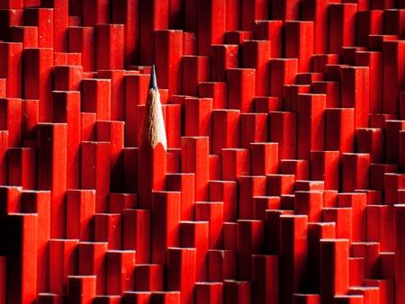 Una matita grafite rossa spuntava di un folto gruppo di matite spuntate. Archivio Fotografico