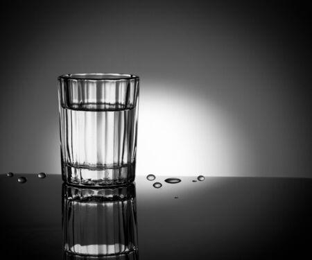 Un bicchiere sfaccettato sul lato sinistro del quadro e gocce d'acqua vicino ad essa in luogo della luce. Archivio Fotografico