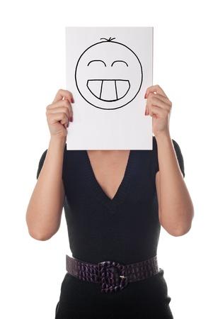 Giovane donna con il sorriso dipinto felice sul foglio di carta sul viso isolato su bianco