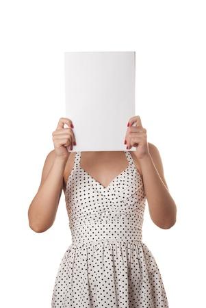 Giovane donna in abito estivo bianco con il foglio di carta bianca sul viso isolato su bianco Archivio Fotografico